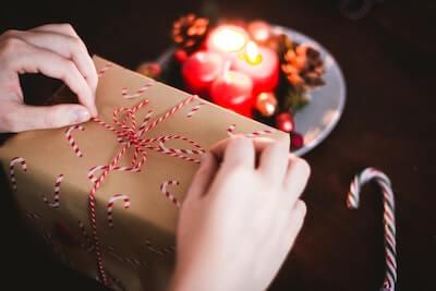 クリスマスプレゼントを開けようとする写真