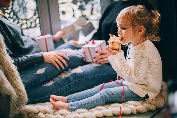 座ってケーキを食べる幸せな子供