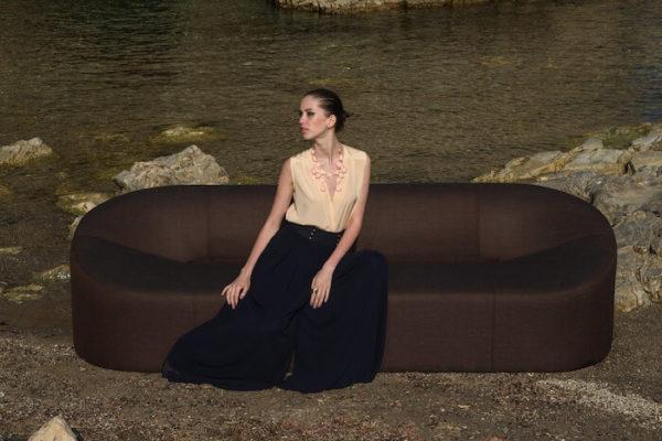 茶色いソファに座る1人の女性
