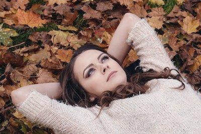 落ち葉の上に寝そべる女性