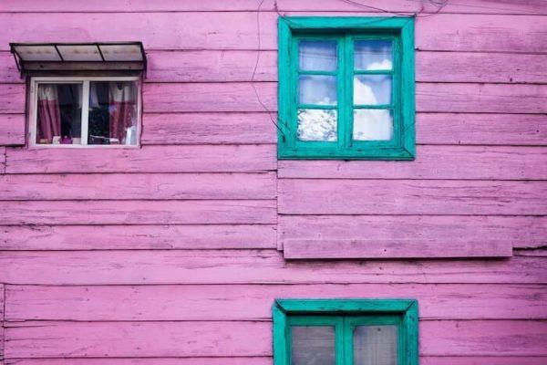 紫の家の外壁と緑の窓枠
