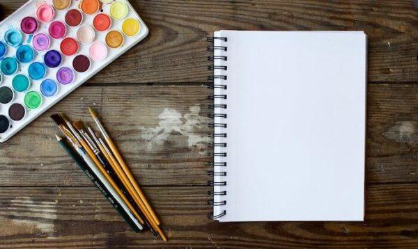 机の上の絵具と筆とスケッチブック