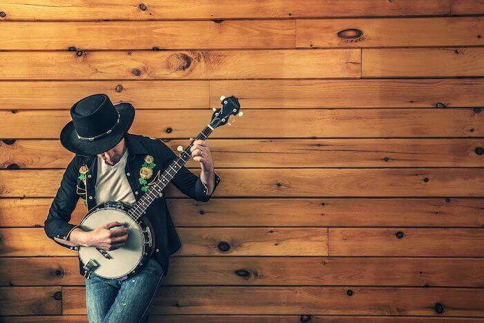 茶色い木の壁にもたれかかったギターを持った人