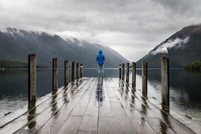 雨の湖の桟橋に立つ人