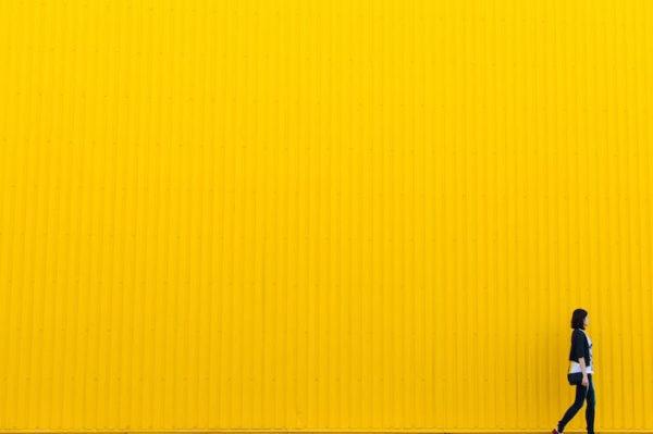 黄色くペイントされた壁とその前を歩く女性