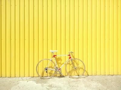 明るい黄色の壁の前に置かれた自転車
