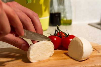 まな板の上でモッツァレラチーズをカットしている