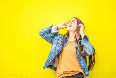 黄色い壁の前で笑う女性