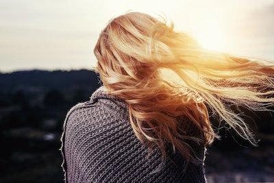 夕陽に映える金髪の女性の後ろ姿