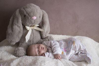 うさぎのぬいぐるみと一緒に寝る赤ちゃん