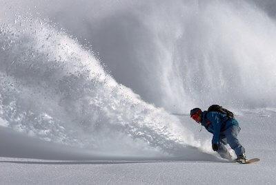 雪煙を巻き上げてスノーボードをする人