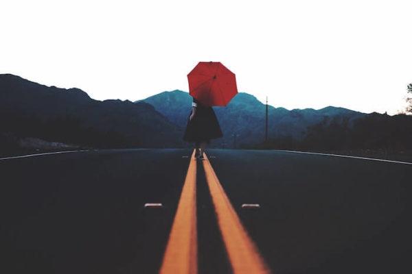 赤い傘をさして歩く女性