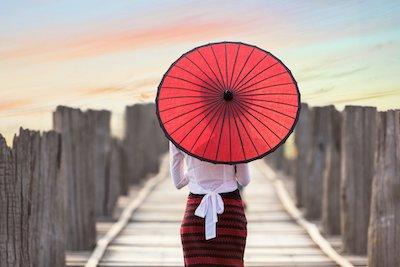 赤い日傘をさす女性の後ろ姿