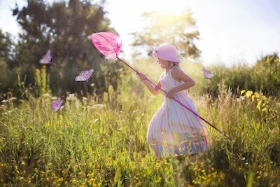 捕虫網を持って蝶を追いかける女の子