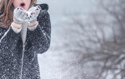 女性が吹く粉雪