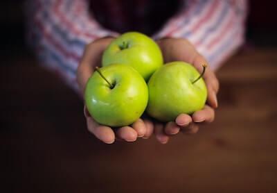 手の上の青リンゴ3つ