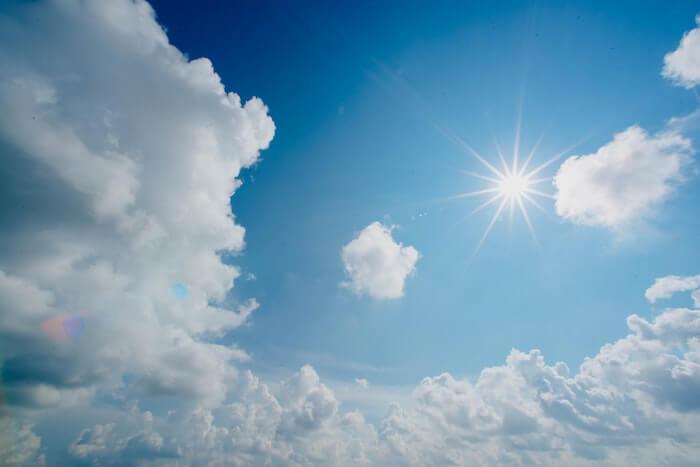 青空と白い雲の間の太陽