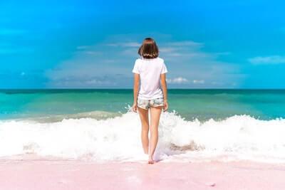 打ち寄せる白波と波打ち際の女性