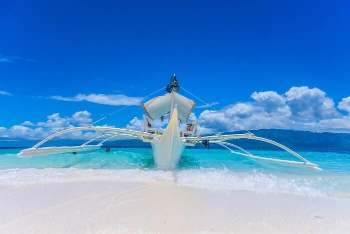 白い砂浜と青い海と白い船