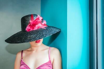 羽飾りのついた帽子を被る女性