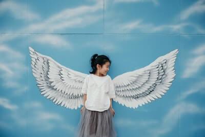 天使の羽の壁画の前で写真を撮る子供