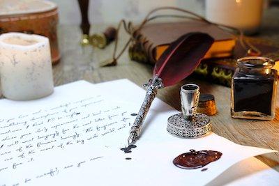 羽ペンと文字が書かれた紙