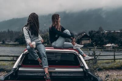 車の屋根に座る女性2人
