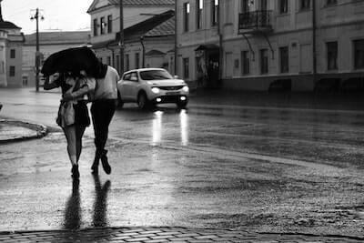 雨の中傘をさして歩く二人