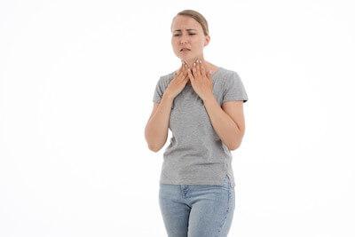 喉の痛みを感じる女性