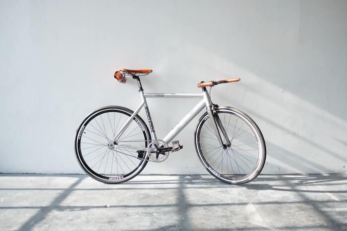 白壁の前のシルバーの自転車