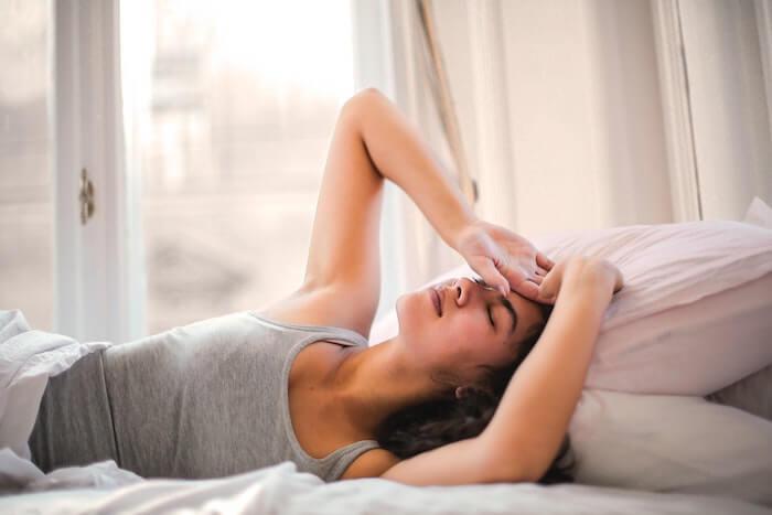 体調を崩してベッドに寝ている女性