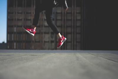 赤いスニーカーを履いて飛んでいる人の足元