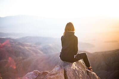 山の頂に腰掛ける女性