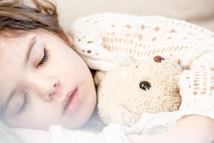 ぬいぐるみを抱いて寝ている女の子