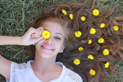 たんぽぽの花で遊ぶ女性