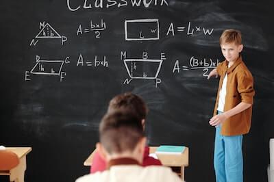 黒板の前で話す小学生