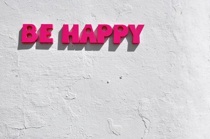 白い壁にBE HAPPYのピンクの文字