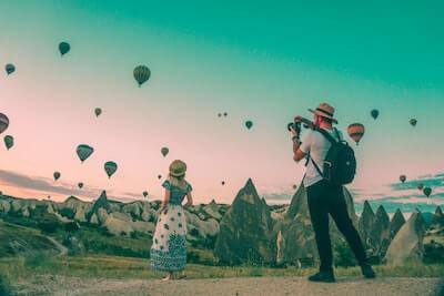 空に浮かぶ熱気球と女性