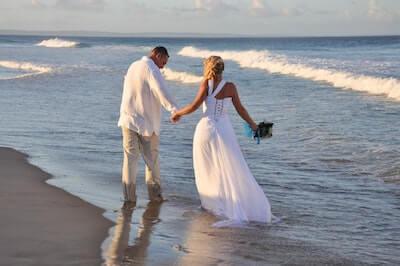 波打ち際で手を繋ぐ新婚の夫婦