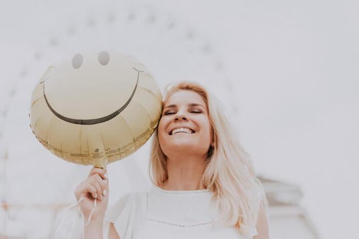 スマイルマークの風船と笑顔の女性