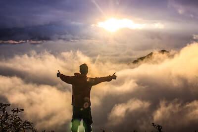 山頂で朝日を迎える男性
