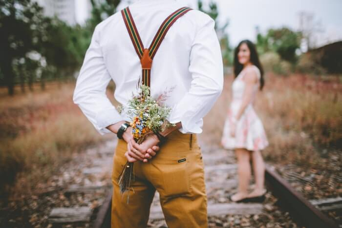 女性に花束を渡そうとする男性