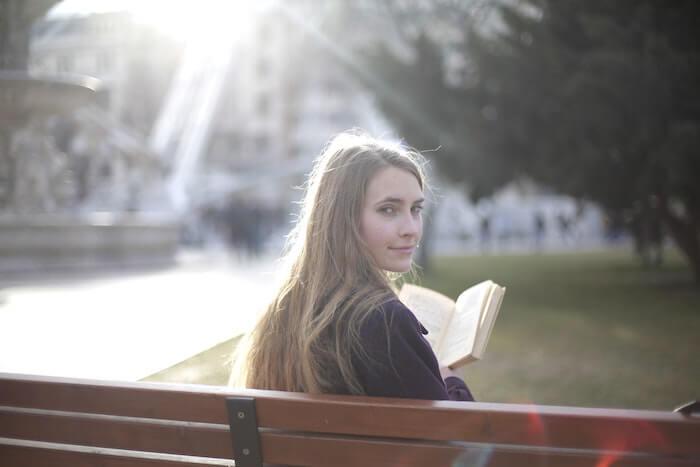 ベンチに座って本を読んでいる女性
