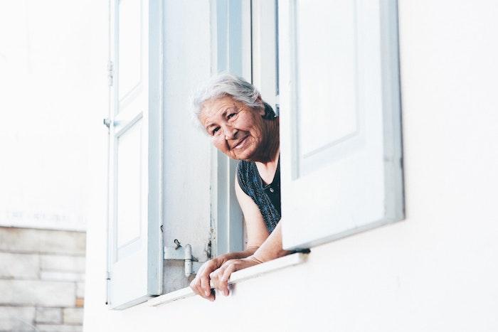 白い家の窓から顔を出すおばあちゃん
