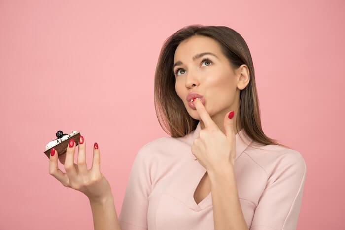 カップケーキを美味しそうに食べる女性