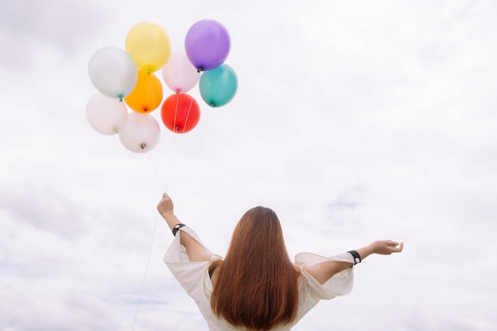 風船を空に話女性