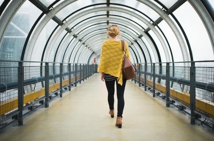 ガラスのトンネルを歩く女性