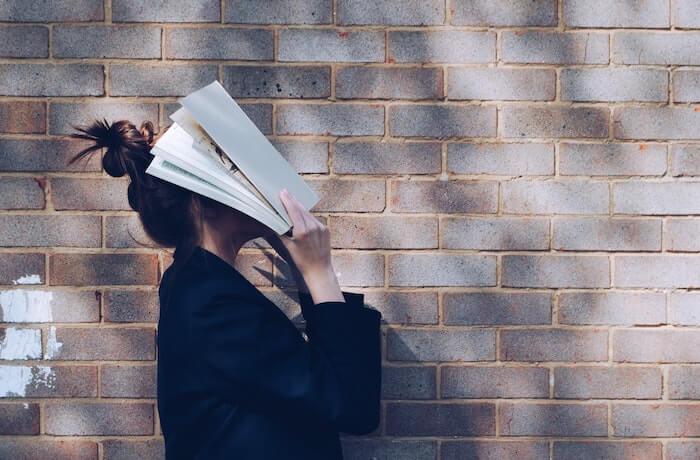 顔に本を被せて練習する女性
