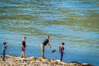 川に石を投げる子供