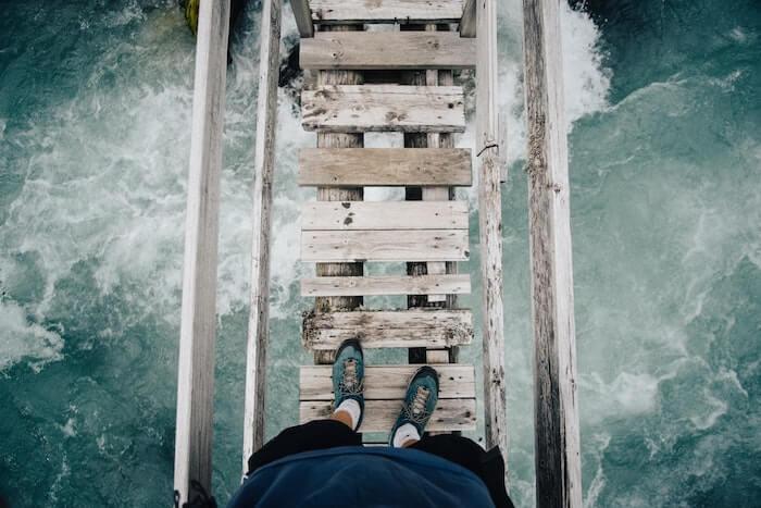 吊り橋の上に立つ人の足